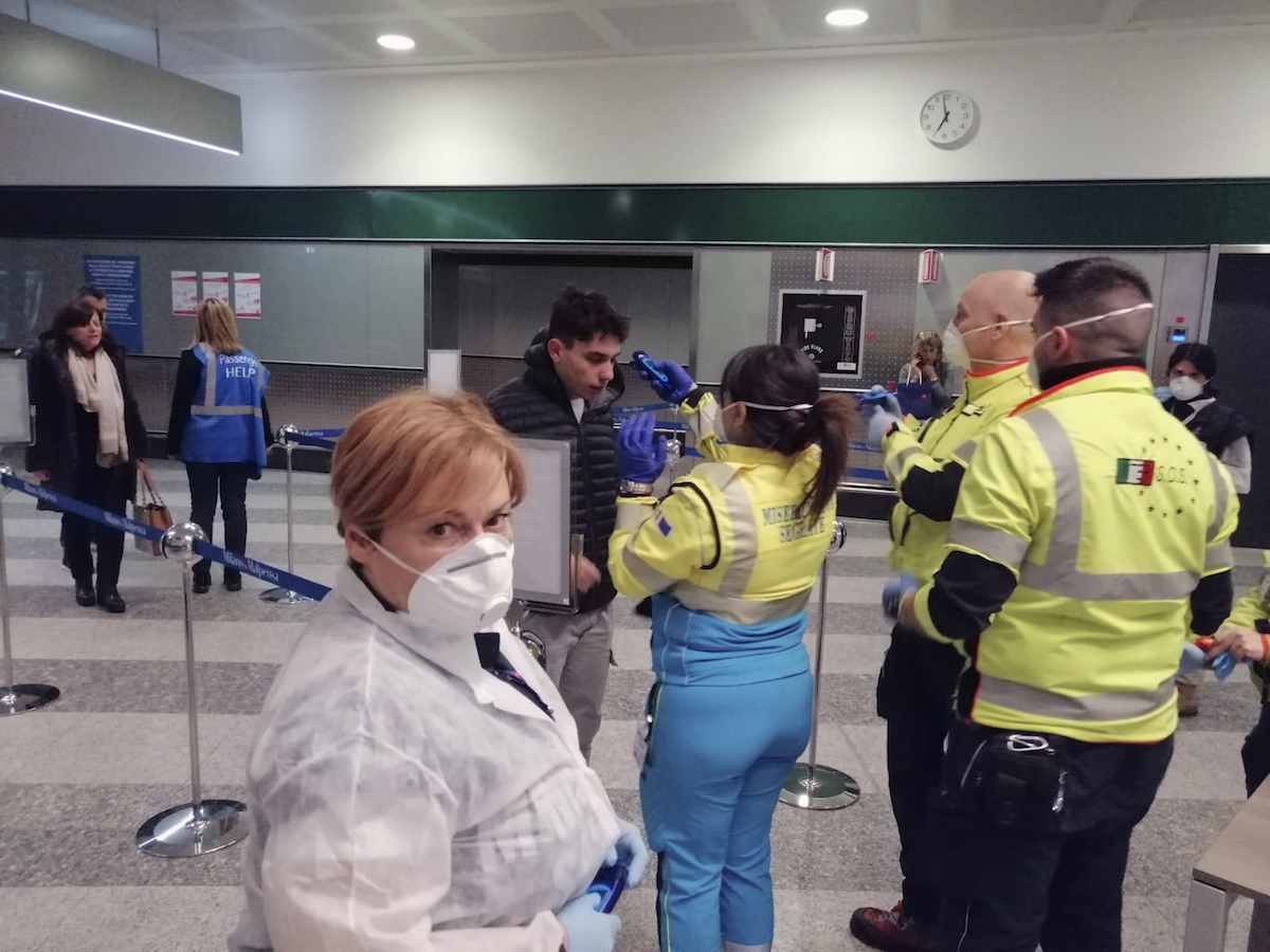 "Civil protection volunteers engaged in health checks at the ""Milano Malpensa"" airport. – Milan, Italy, 5 February 5, 2020 (Dipartimento Protezione Civile/Creative Commons)"