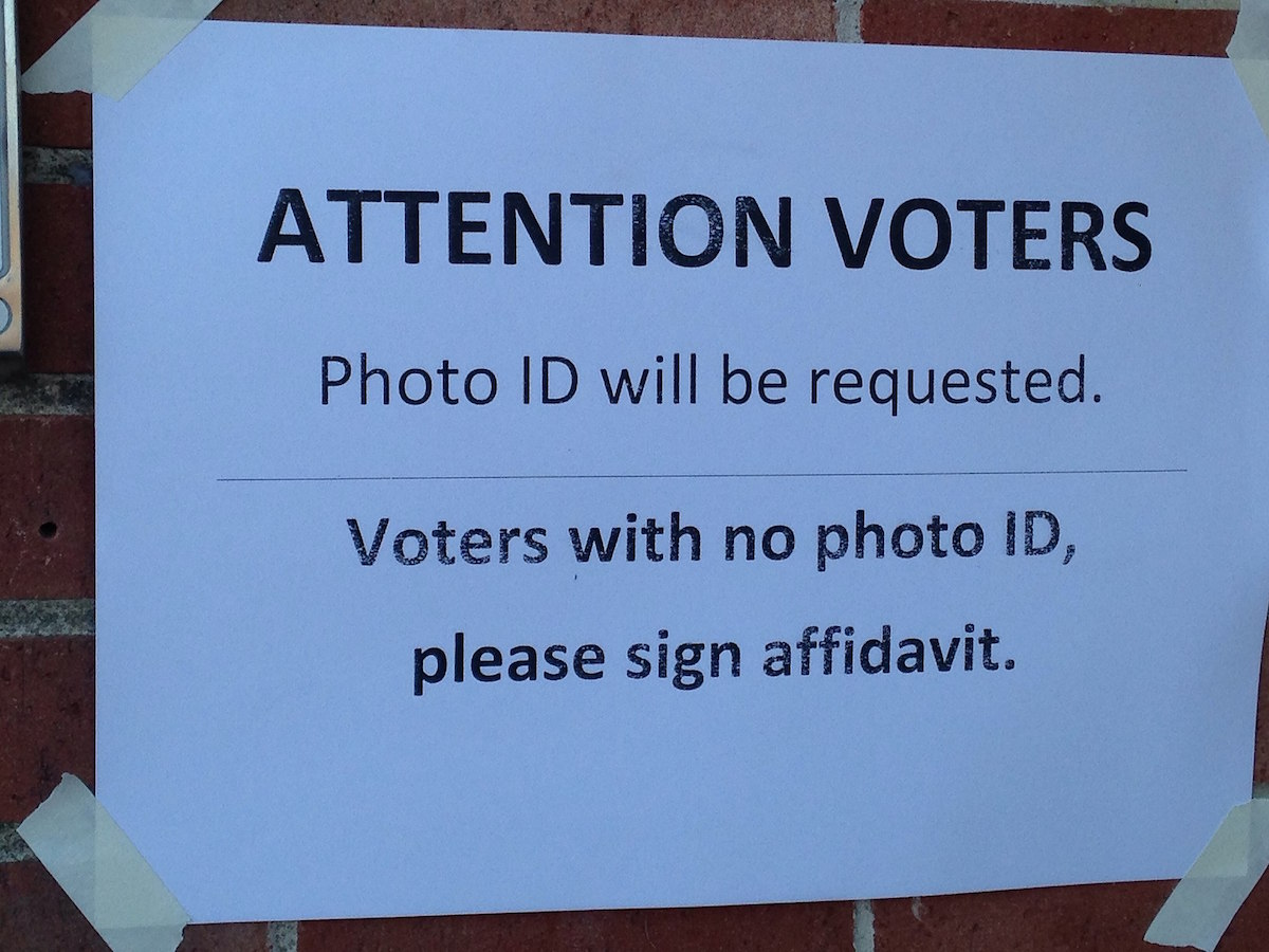 A voter ID warning outside the polling station of Ward 1 in Nashua, New Hampshire – November 5, 2013 (MarkBuckawicki/Creative Commons)
