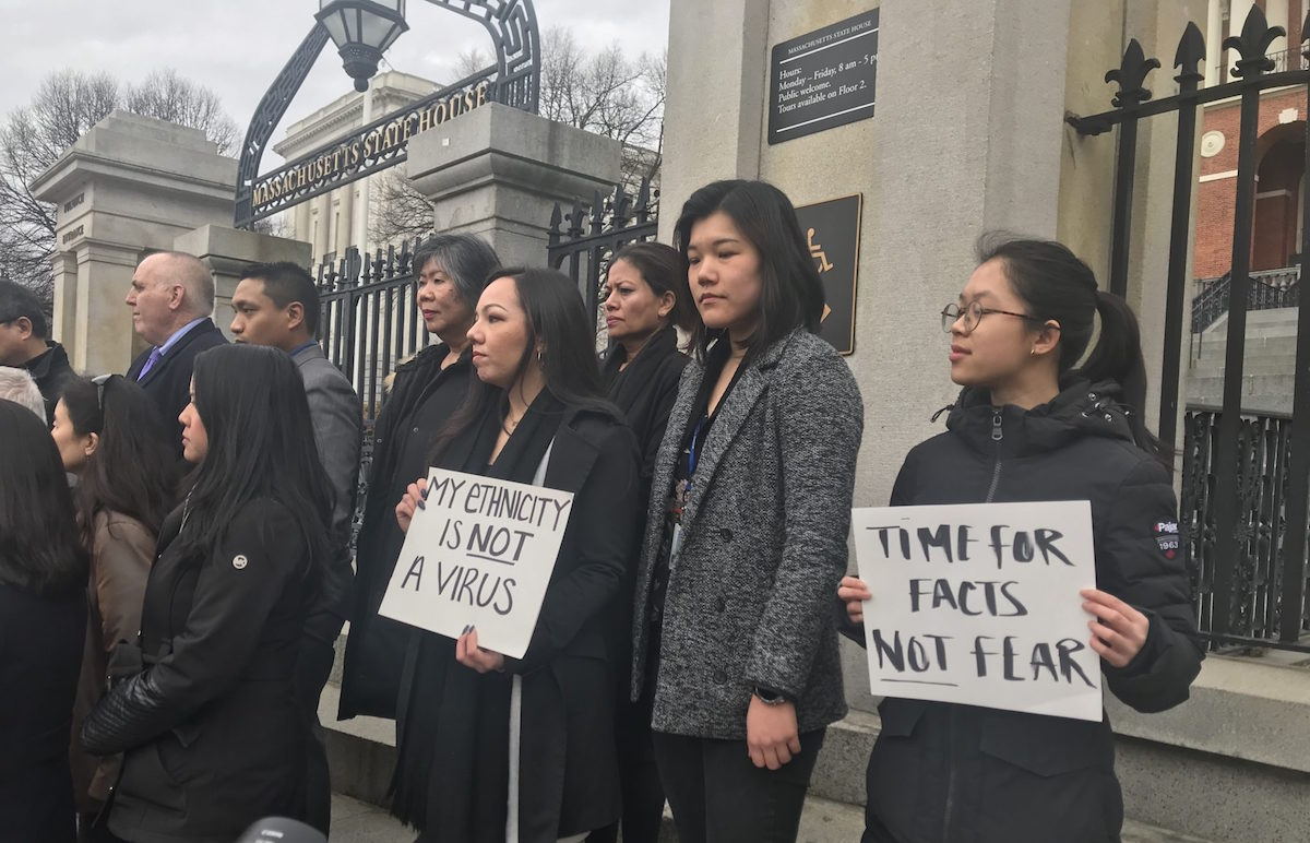 "Jessica Wong, Jenny Chiang, and Sheila Vo, from the state's Asian American Commission, protest on the steps of the Statehouse in Boston – Thursday, March 12, 2020. (Source: <a href=""https://commonwealthmagazine.org/arts-and-culture/virus-notes-discrimination-warning-issued/"">CommonWealth Magazine</a>)"