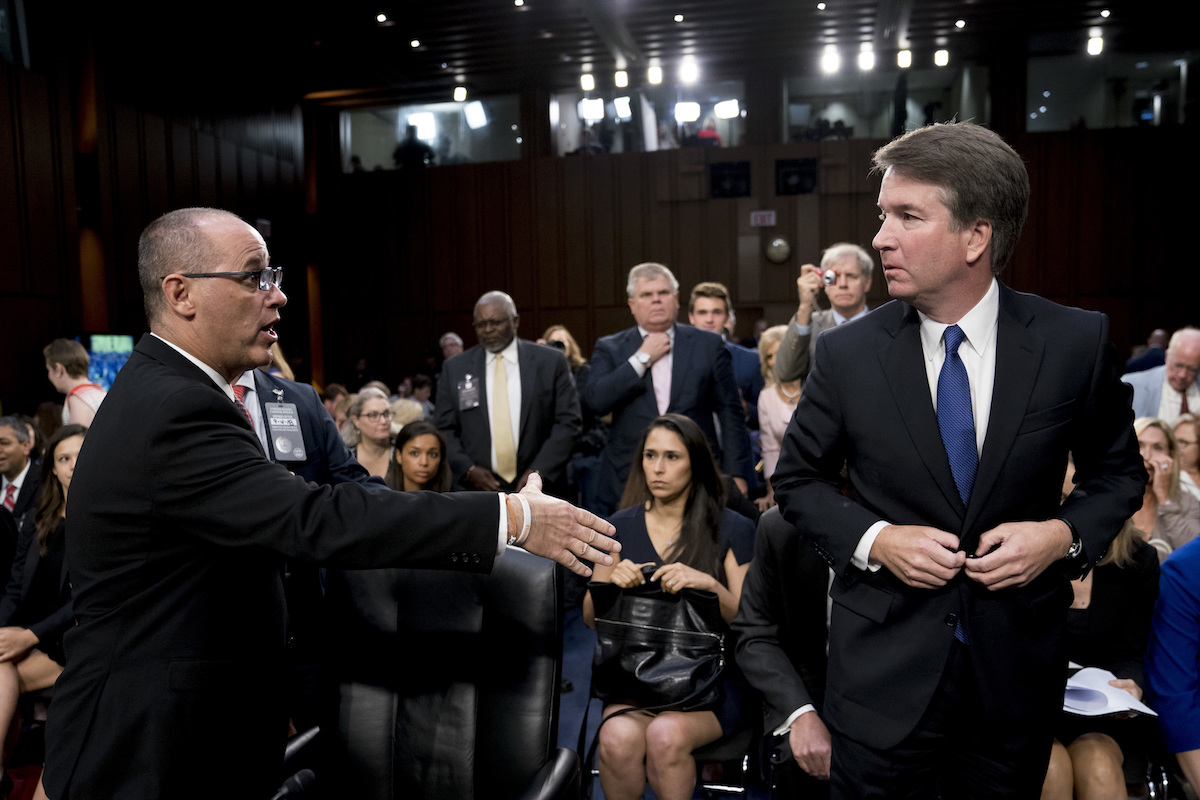 Fred Guttenberg, the father of Jamie Guttenberg who was killed in the Stoneman Douglas High School shooting in Parkland, Fla., left, attempts to shake hands with President Donald Trump's Supreme Court nominee, Brett Kavanaugh, right, at the Senate Judiciary Committee on Capitol Hill in Washington, Tuesday, Sept. 4, 2018. (AP Photo/Andrew Harnik)
