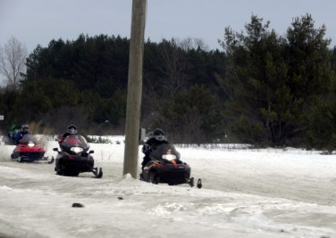 Snowmobilers riding along US-131