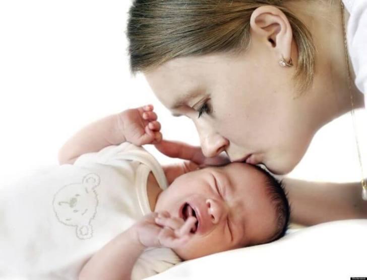 woman kissing kid
