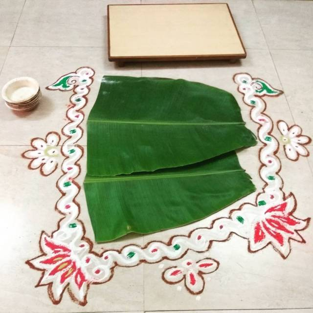 Rangoli kolam around the banana leaf all set to servehellip