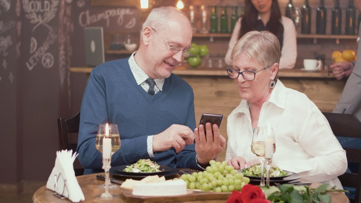 Senior man showing something on his phone to his wife in a restaurant