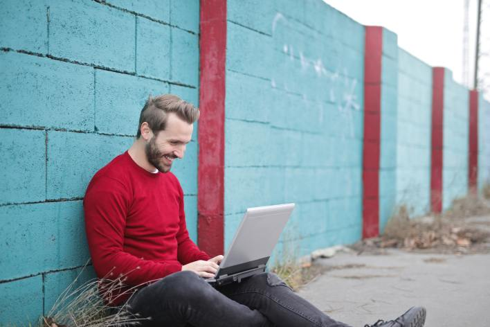 man-leaning-against-wall-using-laptop-941572
