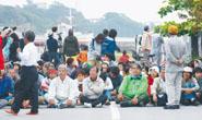 作業車両の進入を阻止しようと漁港入り口で座り込む反対派の市民ら=18日午前5時50分ごろ、名護市・辺野古漁港(伊藤桃子撮影):沖縄タイムス