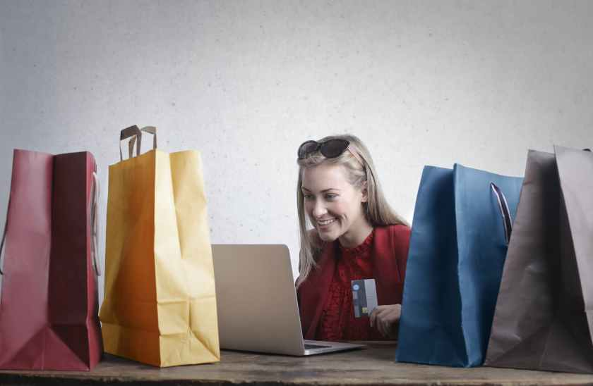 Woman with shopping bags laughing while looking at her laptop while holding her credit card