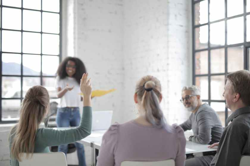female employee raising hand for asking question at conference in office boardroom