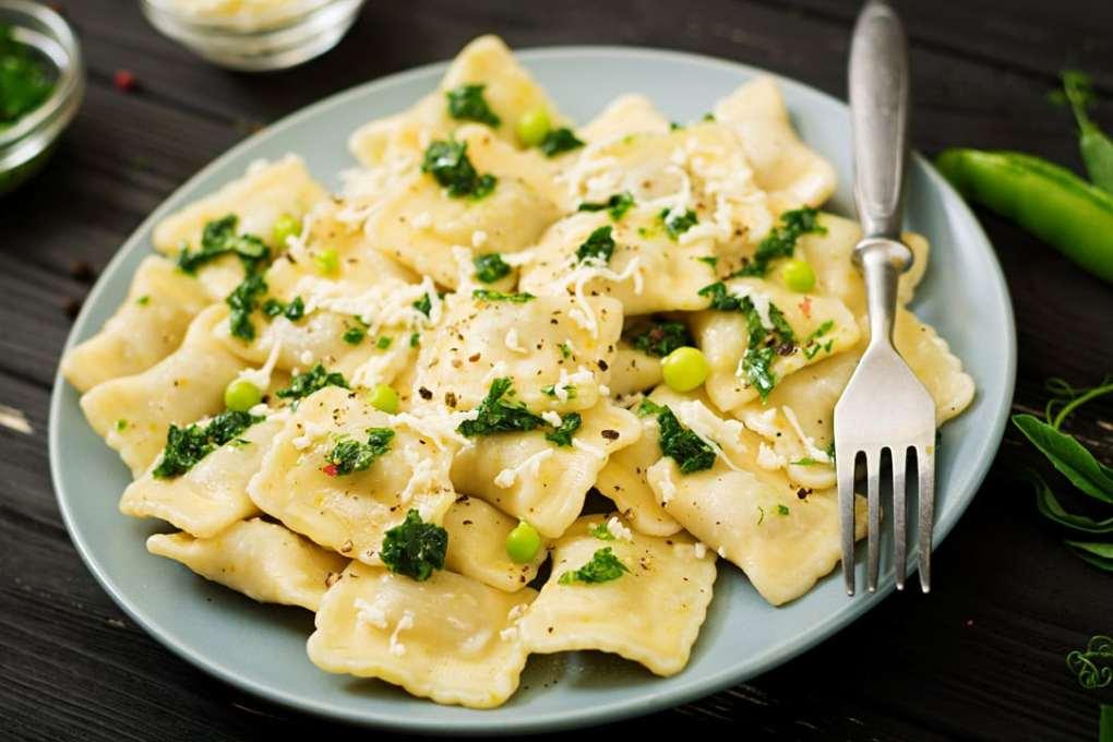 Ravioli auf Teller mit Parmesan und Basilikum Pesto