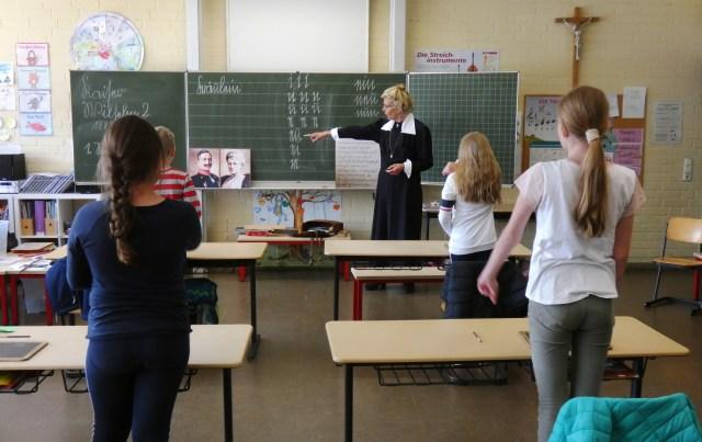 Fräulein Lehrerin steht an der Tafel und erklärt den Kinder die damalige Schreibschrift