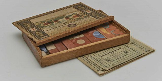 Geöffneter Spielkasten mit braunen, roten, gelben und beige-Farbenen Steinen.
