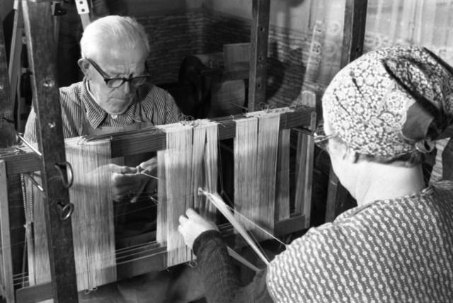 Schwarz-weiß-Foto eines älteren Ehepaars an einem Webstuhl