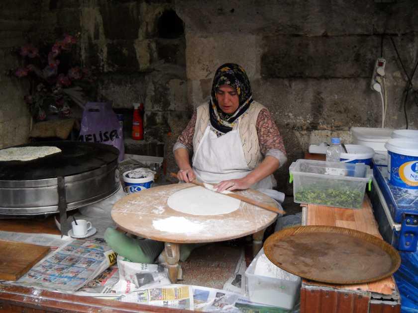 Eine Dame backt frische Gözleme. Sie rollt sen Teig auf einem runden Stein aus.