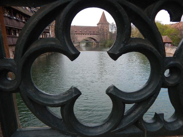 Blick auf den Schlayerturm durch ein rundes Gitter der Brücke in Nürnberg