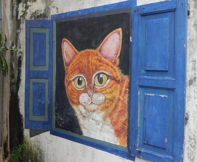 Rote Katze schaut aus dem Fenster, street art penang