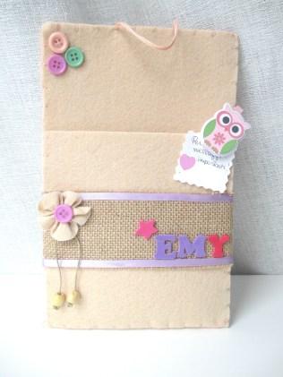 Feltro color rosa carne, fascia in yuta decorata con nastrino lilla in raso. Scritta in fommy. Bottoni colorati. Fiore in feltro con bottone e perline beige in legno.
