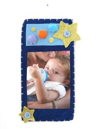 Portafoto da parete in feltro blu, con decorazioni in fommy glitter e pon pon colorati.