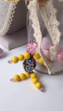 Perline gialle in legno, perlina centrale in resina, tecnica millefiori.