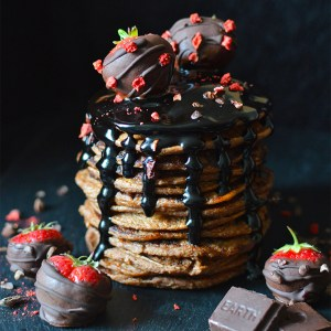 Vegan chocolate chip pancakes, served with raw chocolate sauce and strawberries.