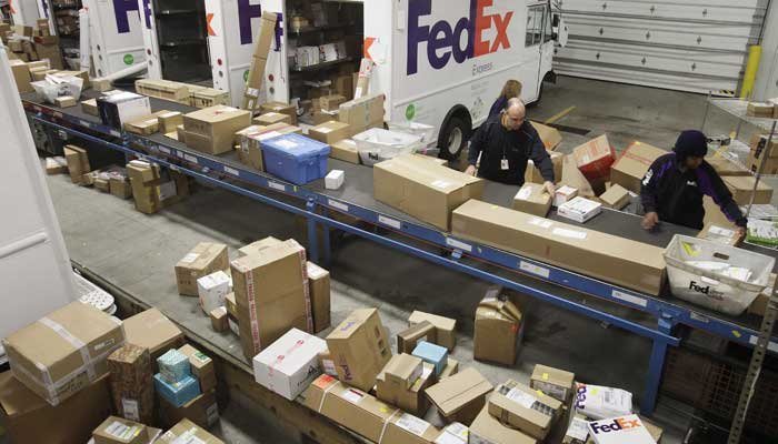 FedEx, UPS and the U.S. Postal Service all expect to ship record amounts of packages this year. Here FedEx employees pull boxes from a conveyor belt to fill their delivery trucks in a sorting facility in the Bronx. (Source: AP Photo/Mark Lennihan)
