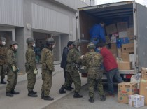 Steve Zimmer (blue jacket), James Mercer (red jacket) and Kazuo Iwagami (taking photos) unload food and supplies at a relief center near Onagawa, Japan.
