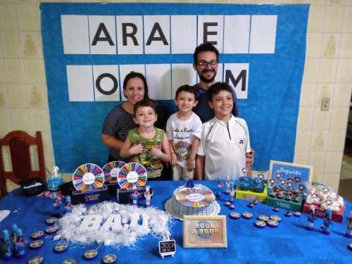 menino que fez aniversário com o tema Roda a Roda na mesa do bolo com os pais e irmãos