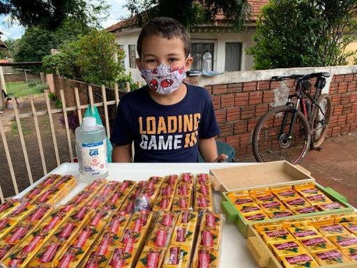 menino vendendo paçoquinhas frente casa