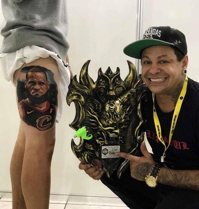 tatuador segurando troféu ao lado homem tatuagem lebron james