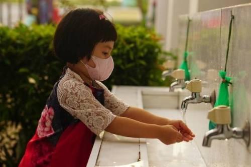 menina oriental lavando a mão