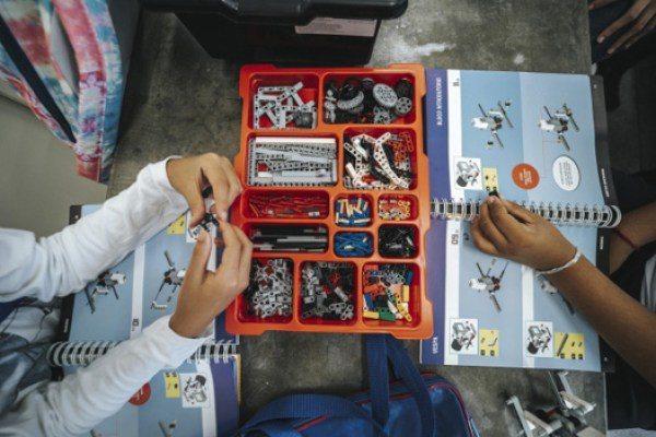 alunos manuseando peças robô aula robótica programação escola pública