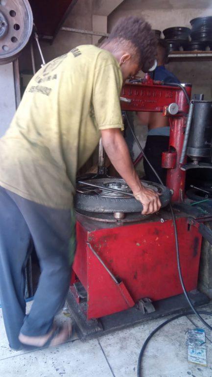 Jovem de camisa amarela trabalhando em borracharia