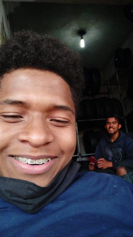 Jovem borracheiro sorrindo em selfie dentro de borracharia com irmão no segundo plano da foto