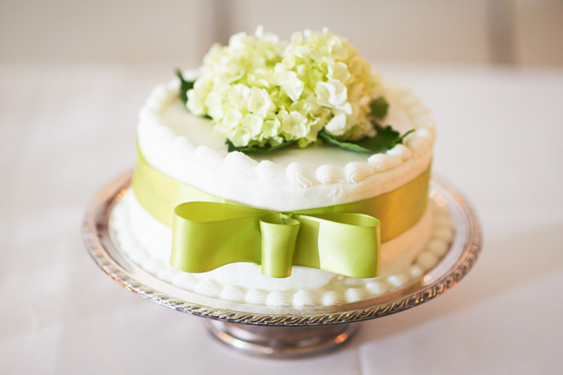 wedding cake with green bow and flower arrangement