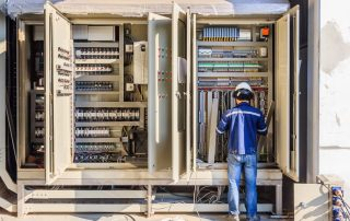 Industrial electrician on the job check wiring on PLC cabinet