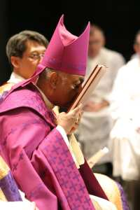 During the Feb. 21 Rite of Election and the Call to Continuing Conversion at the Atlanta Civic Center, Archbishop Wilton D. Gregory acknowledges the names in the Book of the Elect with a prayerful kiss of peace.