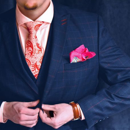 Men's luxurious silk handmade necktie with red paisley pattern on pink and white background