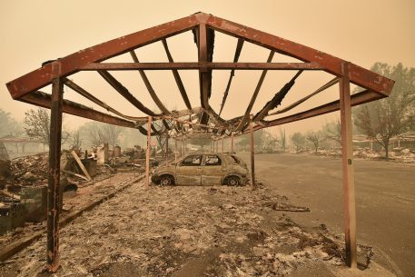 Burned out vehicles are surrounded by smoldering rubble while firefighters continue to battle the Valley fire in Middletown, California on September 13, 2015