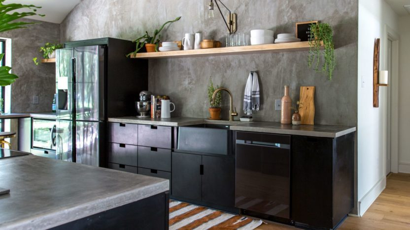 The kitchen has cement countertops and light wood shelving
