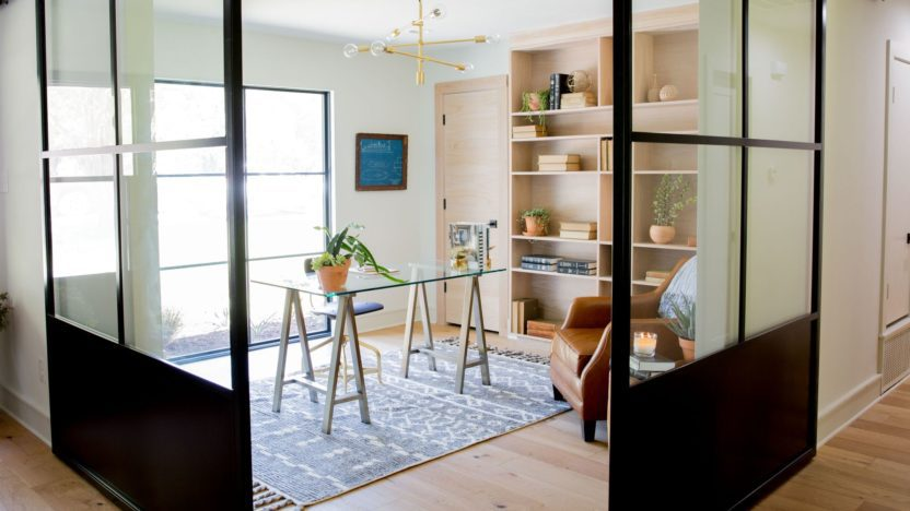 Sliding glass doors with black metal frames divide the office from the rest of the house