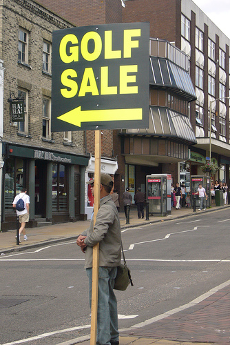 "Picture of man holding ""Golf Sale"" sign for absolutely no reason."