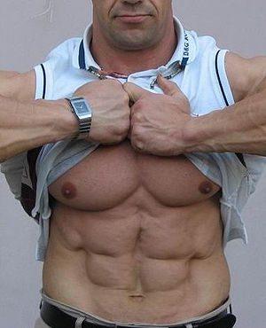 English: A man lifts his shirt up to expose hi...