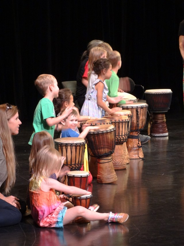 "The audience takes their turn at playing the ""djembes."""