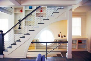 Modern custom cable rail staircase system with custom cabinetry and a nautically-inspired window behind