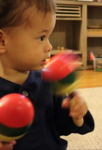 Toddler using maracas to follow hid musical interests.