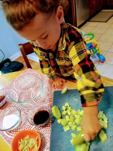 Toddler helping to prepare a meal. A great way to get a picky eater to eat what you serve.