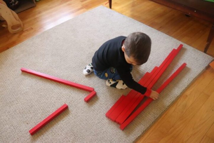 Child working with the Montessori Red Rods.