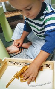 child exploring minature musical instruments