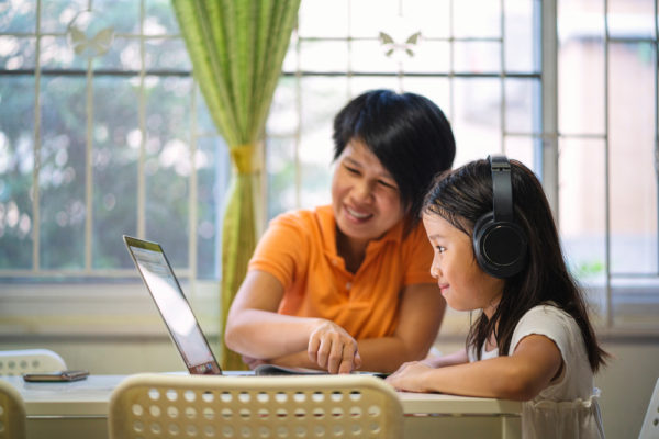 Mother helping her child with online learning