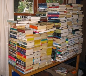 Books piled several feet high, covering a table