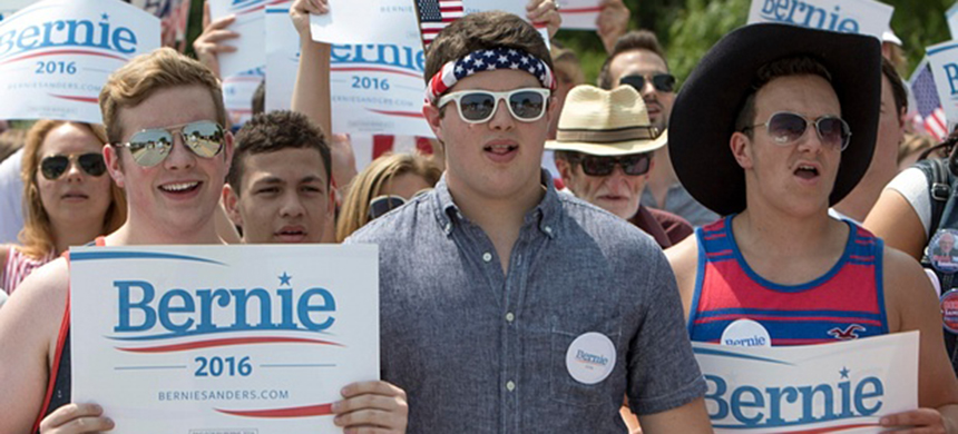 Supporters of Democratic presidential hopeful senator Bernie Sanders hold signs during a Fourth of July parade on Saturday in Waukee, Iowa. (photo: Scott Morgan/Reuters)